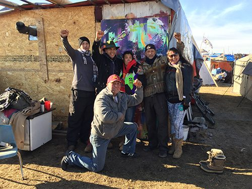 Artist Yatika Starr Fields (second from the left near his painting) poses with admirers of his work at Oceti Sakowin Camp, North Dakota.